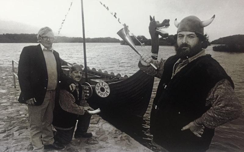 Mick O'Brien launching the Killarney Viking boat with boatbuilders David Gleeson and Dermot Mahony